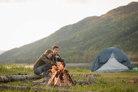 Young couple sitting near campfire at campsite