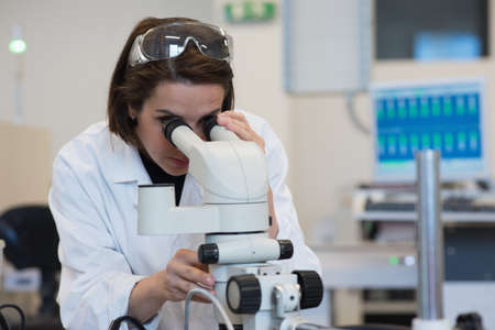 Female technician researcher looking through microscope in laboratory