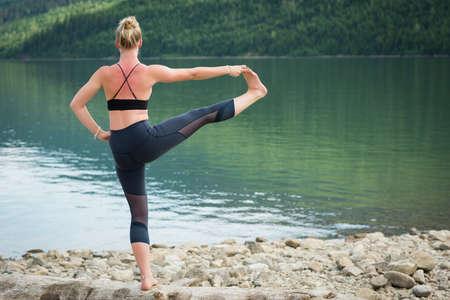 hasta: Rear view of young woman practicing Utthita Hasta Padangusthasana on log at lakeshore