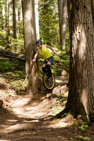 Woman unicycling amidst trees in forest LANG_EVOIMAGES