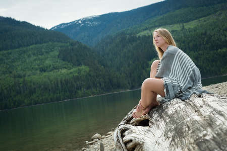 Side view of young woman sitting on log at lakeshore