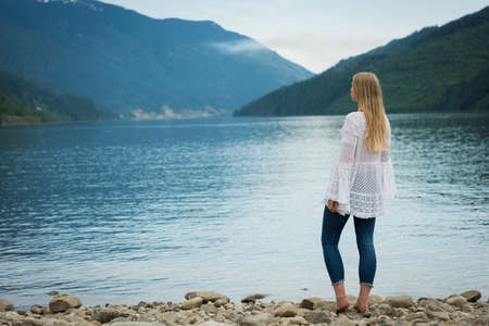 Rear view of woman standing at lakeshore while looking at mountains