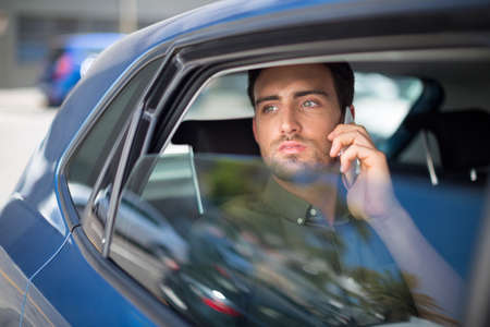 transportation: Man talking on mobile phone while traveling in car LANG_EVOIMAGES