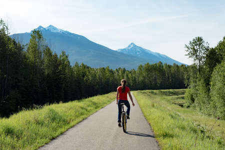 Rear view of woman riding unicycle on road against mountains