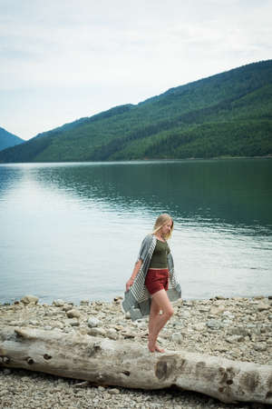 Young woman walking on log at lakeshore against mountains LANG_EVOIMAGES