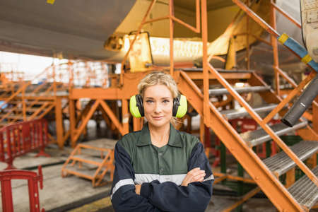 Portrait of female aircraft maintenance engineer standing with arms crossed at airlines maintenance facility LANG_EVOIMAGES