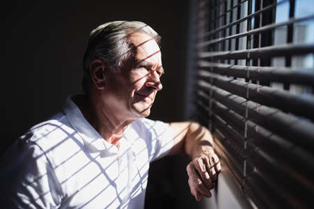 Thoughtful senior male patient looking through window at hospital ward LANG_EVOIMAGES