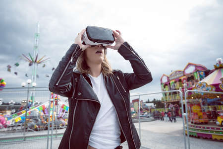 Woman using virtual reality headset in amusement park