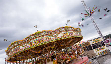 Merry-go-round and swing ride in amusement park at day LANG_EVOIMAGES