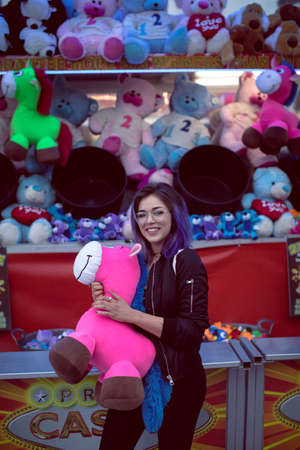 clothing store: Portrait of beautiful woman holding soft toy in amusement park