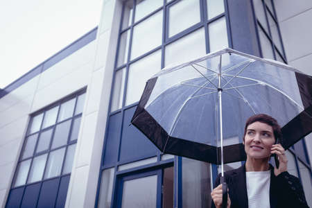 company premises: Businesswoman holding umbrella while talking on mobile phone in office premises