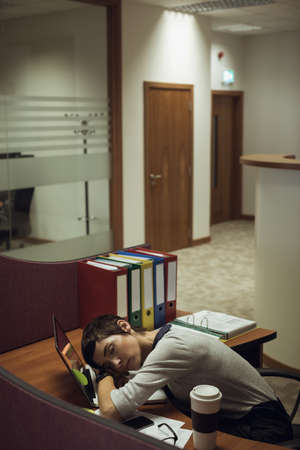 overburden: Tired businesswoman leaning on desk in office LANG_EVOIMAGES