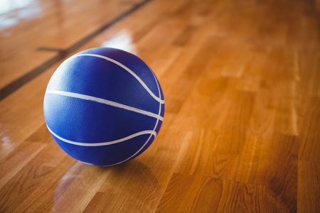 Close up of blue basketball on hardwood floor in court Stock Photo