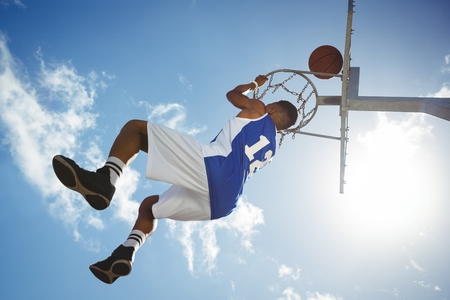 Low angle view of male teenager hanging on basketball hoop against blue sky
