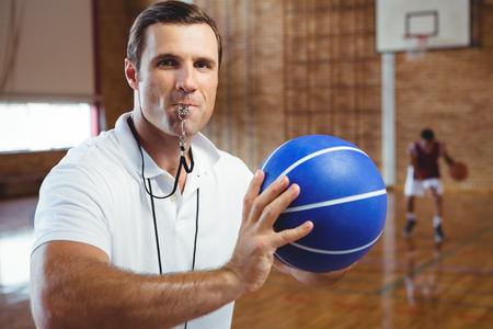Retrato del entrenador que silba mientras que sostiene baloncesto en la corte Foto de archivo - 82345496