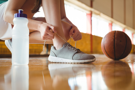 Close up of woman tying shoelace while crouching on floor in basketball court Stock Photo