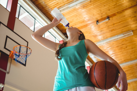 Low angle view of woman drinking water while standing in basketball court