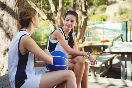 Female friends talking while sitting with basketball on seat in court Stock Photo