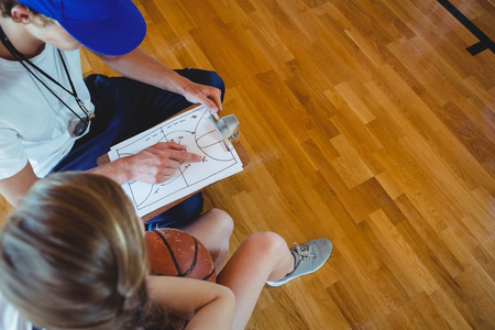 High angle view mannelijke coach uitleggen diagram voor vrouwelijke basketballer tijdens het zitten in de rechtbank Stockfoto - 82345904