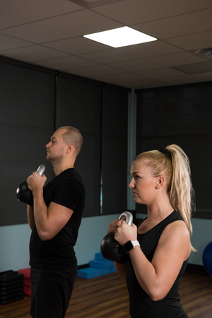 Young friends exercising together with kettle bells at gym