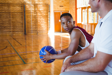 Basketball player looking at coach while sitting on bench in court