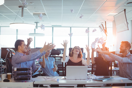 ceiling: Cheerful business people tossing crumpled paper balls at desk in office