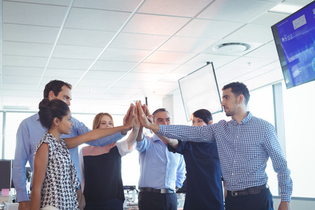 ceiling: Business colleagues putting their hands together at office Stock Photo