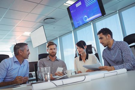 ceiling: Tilt image of business people discussing at desk in office Stock Photo