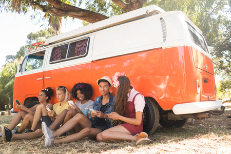 Happy fiends using phone while sitting by camper van on field Stock Photo