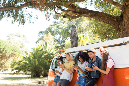 Fiends using smartphones while standing by camper van on sunny day Stok Fotoğraf