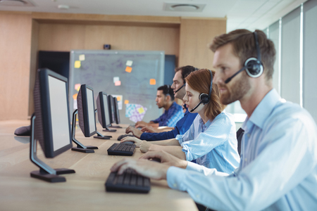 customer service representative: Side view of business people working at desk in call center Stock Photo