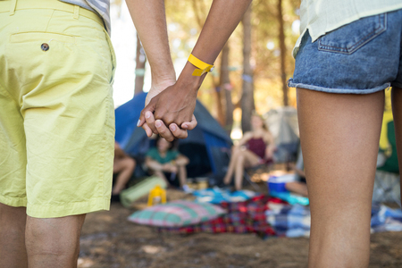 carrying: Close up of couple holding hands while standing at campsite Stock Photo