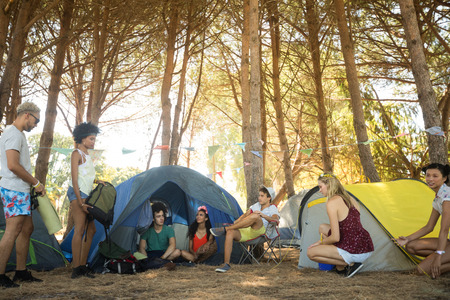 adventuring: Friends by tents on field at campsite