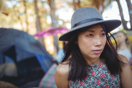 Thoughtful young woman wearing gray hat at campsite Stock Photo