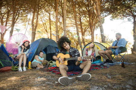 Young man playing guitar while friends sitting by tents at campsite