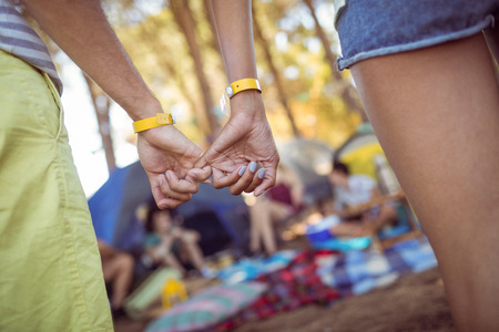 Cropped image of couple hooking pinky fingers while standing at campsite