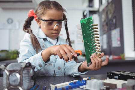 Concentrated elementary girl assembling circuit board on desk at electronics lab Stock Photo