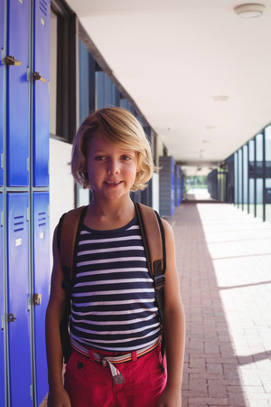 ceiling: Portrait of smiling schoolboy standing by lockers in corridor at school Stock Photo