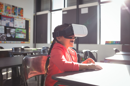 Girl using virtual reality glasses in classroom at school