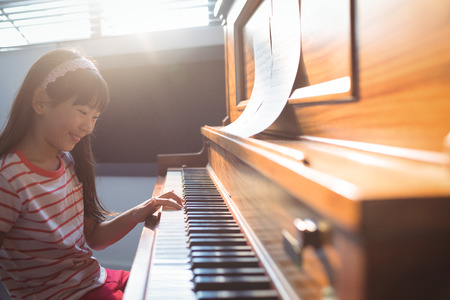 Smiling girl practicing piano in class at music school