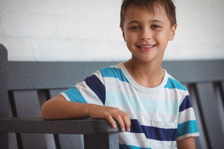 Portrait of smiling boy sitting on bench at school