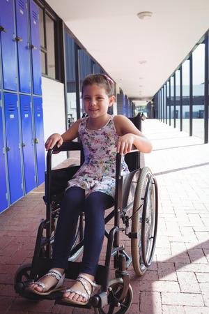 Portrait of smiling schoolgirl sitting on wheelchair in corridor at school