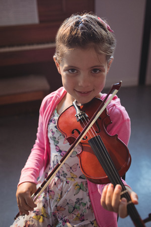 Portrait of girl student rehearsing violin in music class Stock Photo