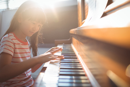 Smiling girl practicing piano in classroom at music school Foto de archivo