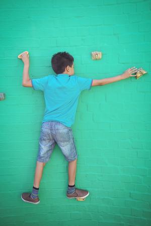 Full length rear view of boy climbing on green wall