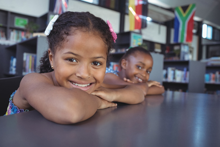 Close up portrait of smiling girls leaning on desk in library Banco de Imagens