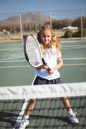 Portrait of girl playing tennis on court during sunny day Stock Photo