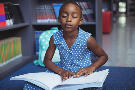 Girl reading braille book while sitting in library Foto de archivo