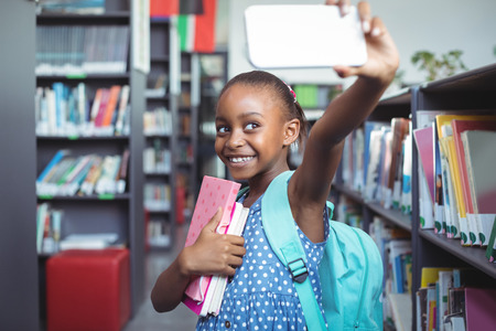 Smiling girl taking selfie while standing by bookshelf in library