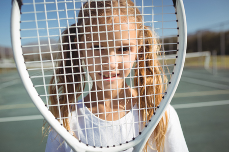 multi tasking: Close up portrait of girl seen through tennis racket Stock Photo